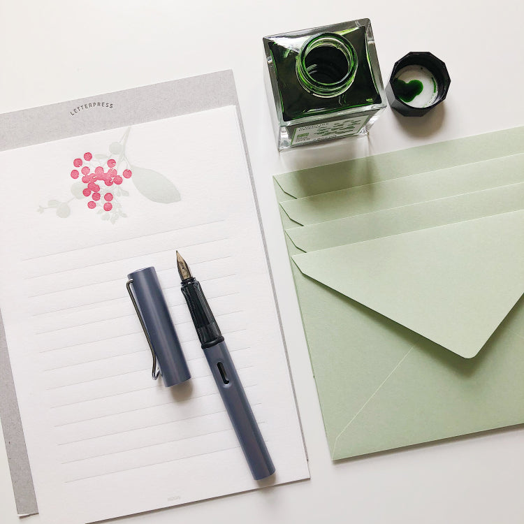 A fountain pen rests on a notepad. A green inkwell is at the top of the image with green envelopes to the right.