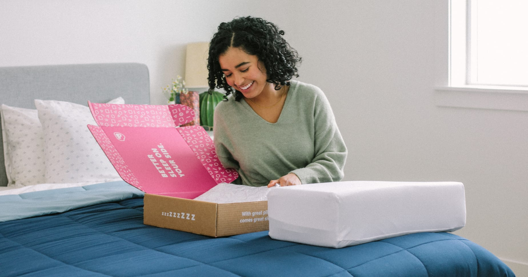 A Pillow Cube customer unboxing their purchase on their bed