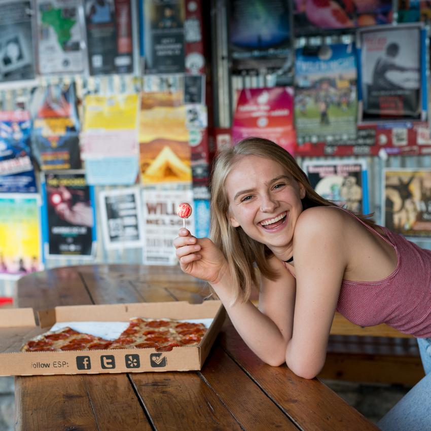 Woman smiles holing a lollipop in a pizza parlour