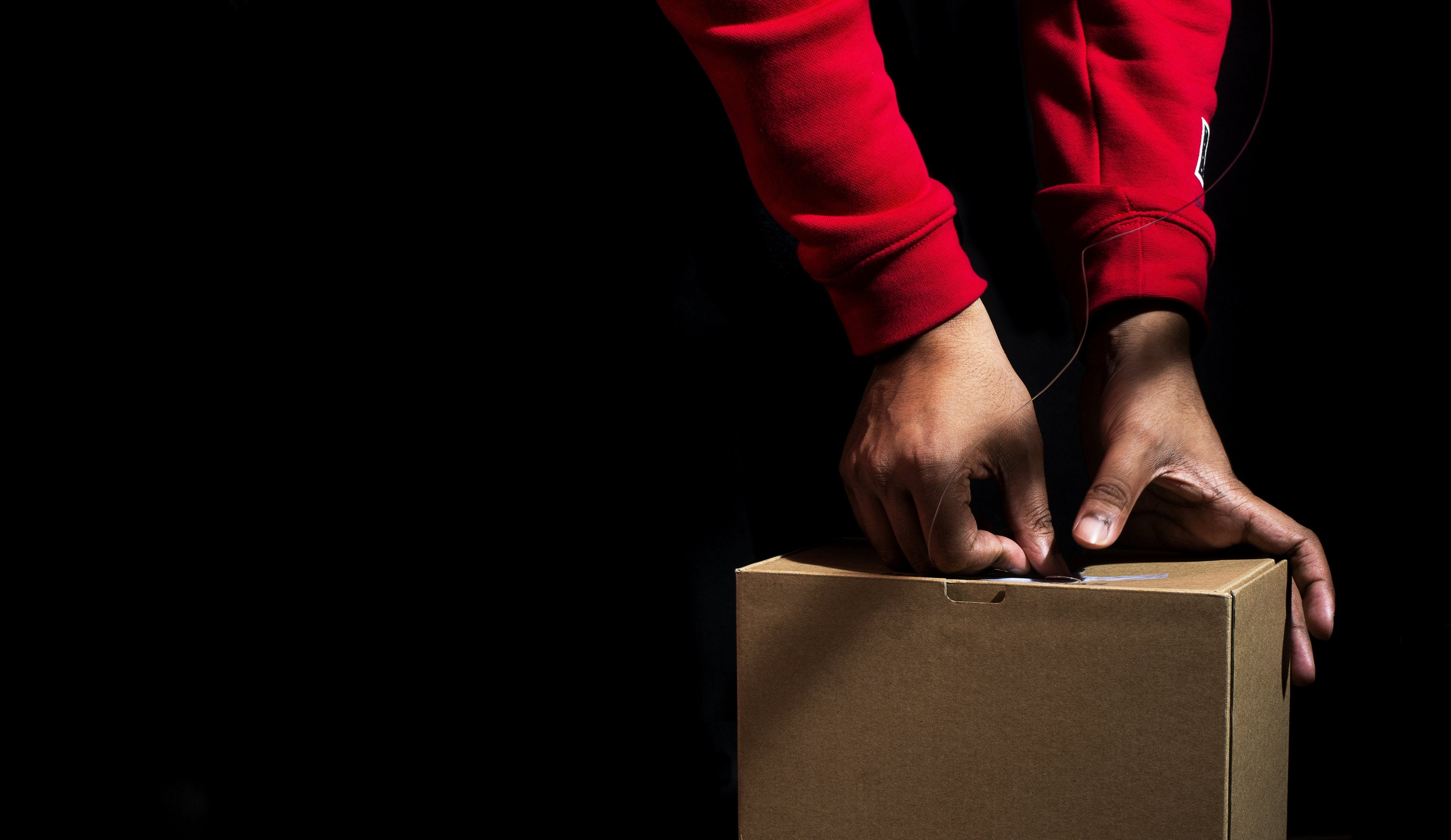 Image of a hands sealing a cardboard box with tape ready for shipping to the customer