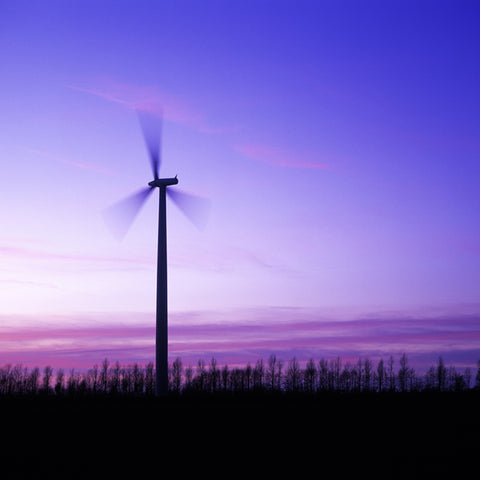Modern windmill against a purplish-blue twilight sky