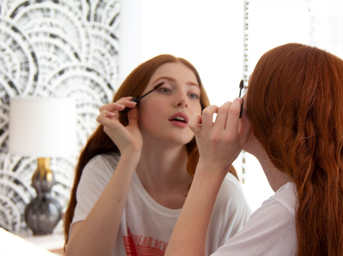 A woman with red hair applies makeup in a mirror