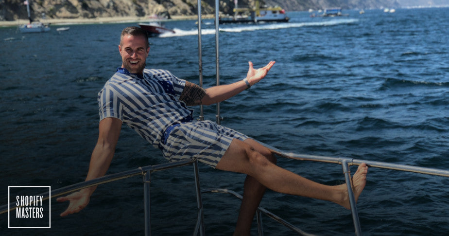 Male model wearing a Romperjack stripped romper on a boat.