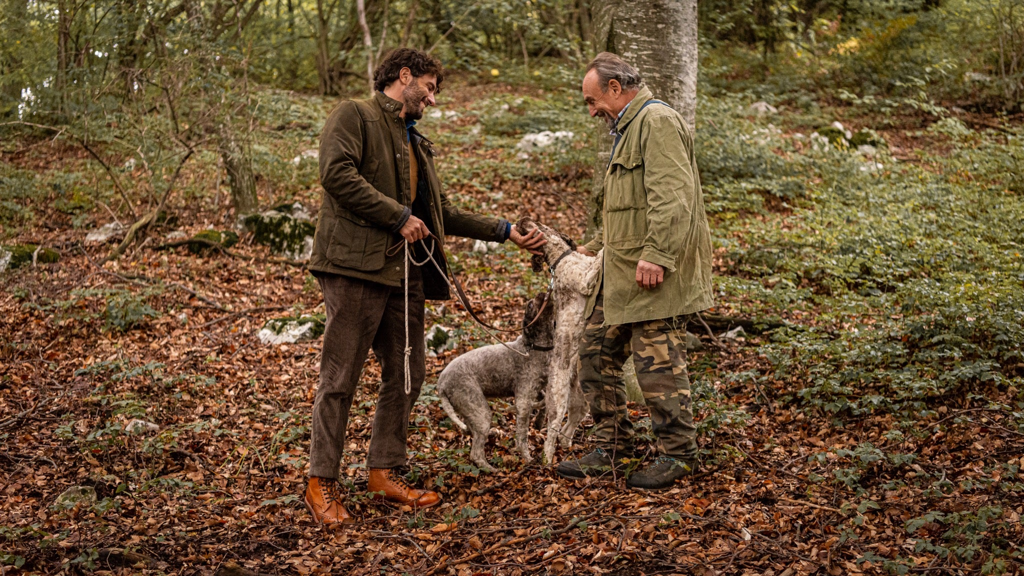 Two men walking their dog in the woods while wearing shoes by Velasca.