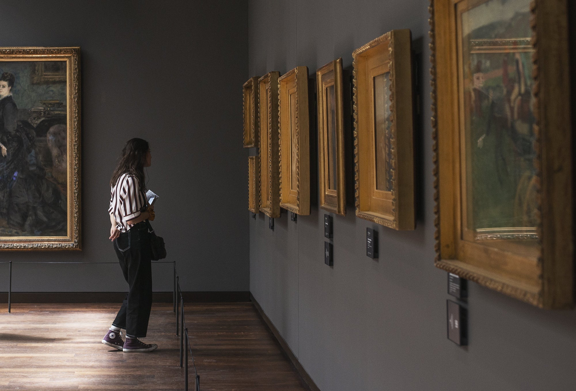 A woman looks at art in a gallery