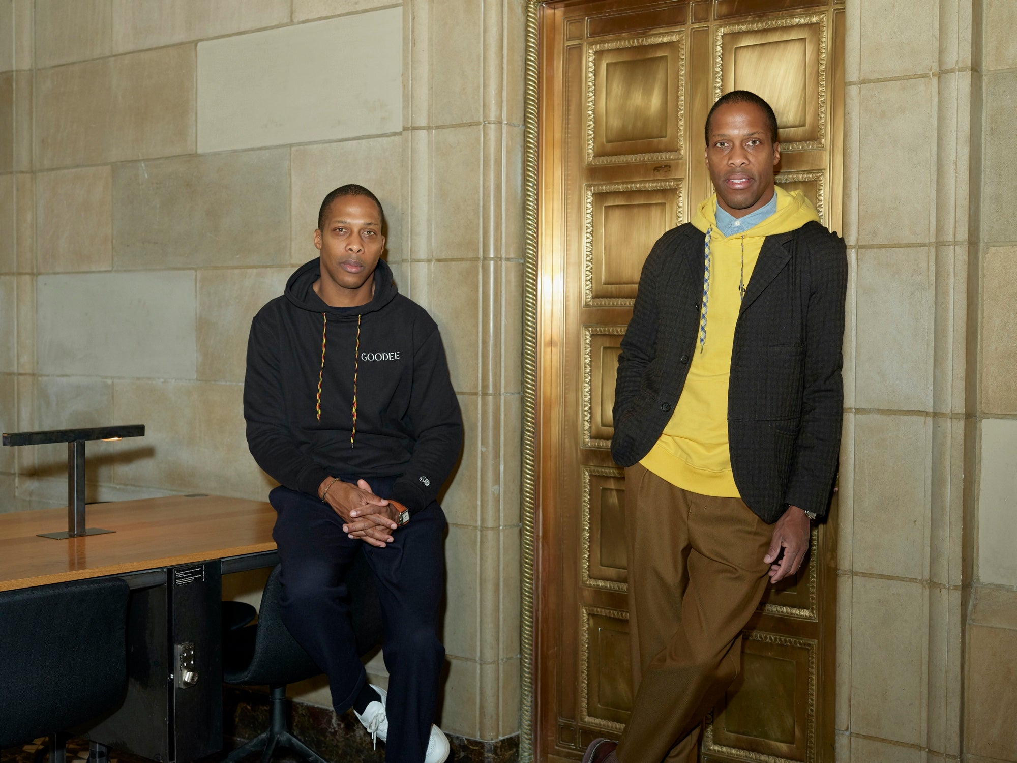 Portrait of Byron and Dexter Peart wearing casual clothes and leaning in a doorway