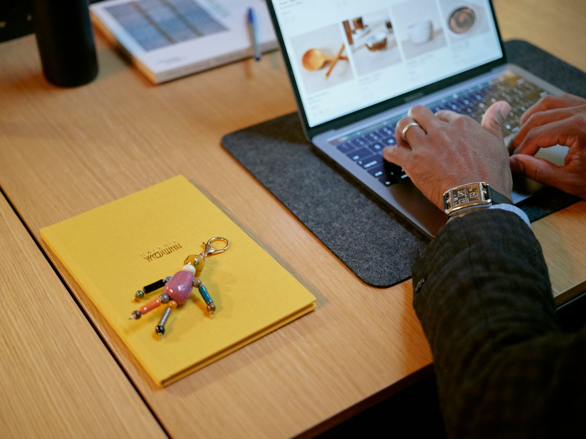 Close up of hands on a computer with a notebook and keychain on the table next to the computer