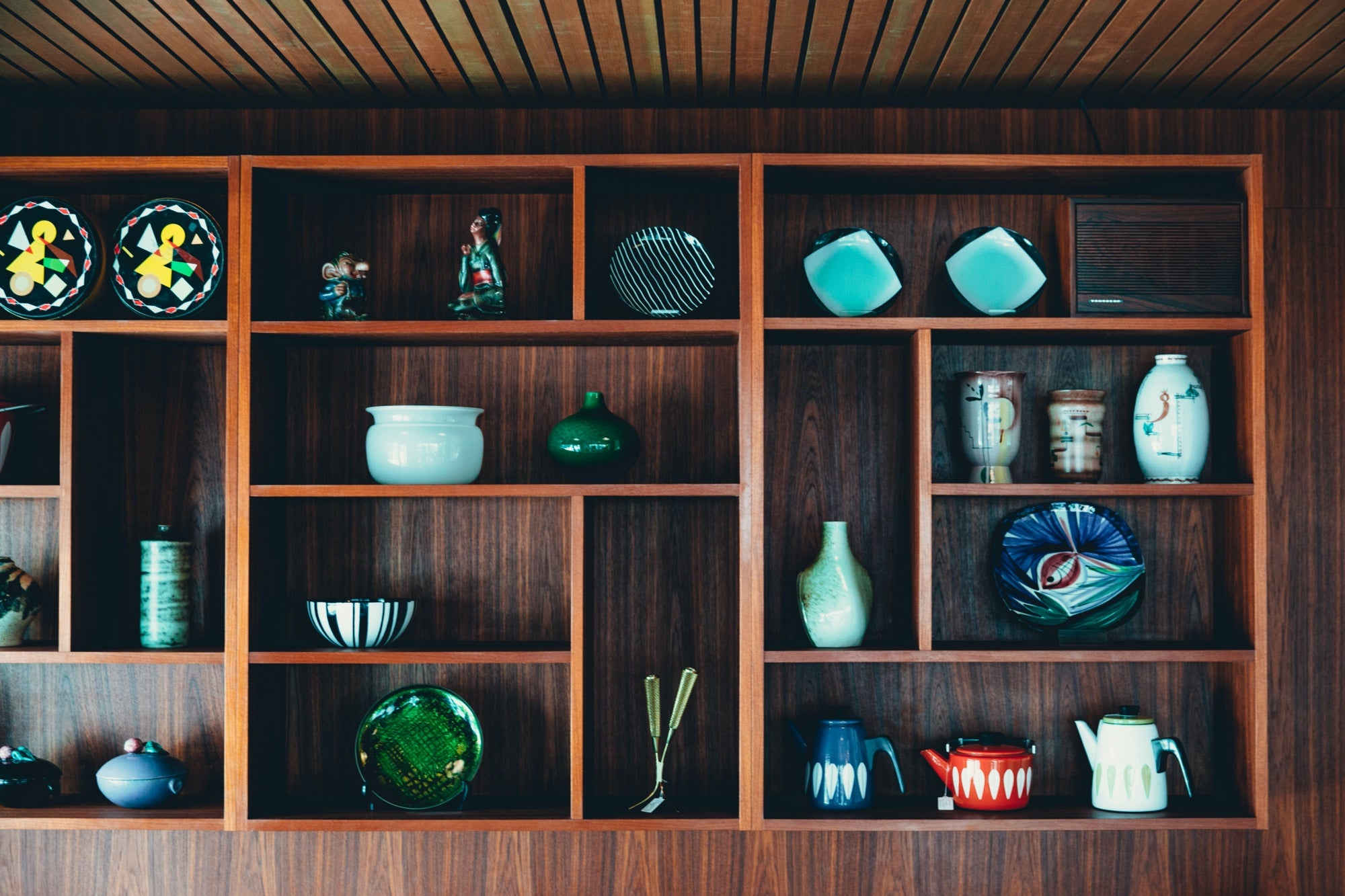 Wall shelf covered in ceramic vases and decorative objects