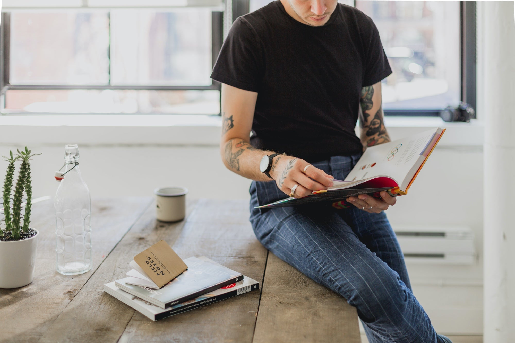 Man with tattoos sits on a table thumbing through a book