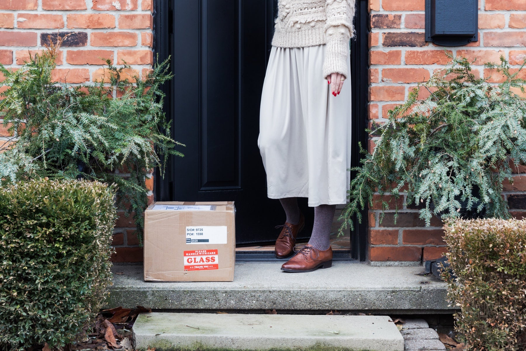 Woman stands at a front door flanked by bushes. A package waits for her on the stoop