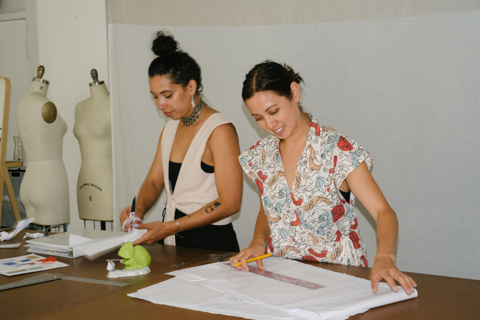 The founders of Selva Negra work side by side at a table with garment production materials around them