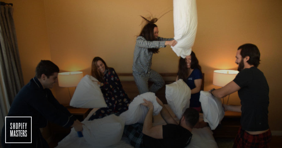 Six adults having a pillow fight using Sheets & Giggle products.