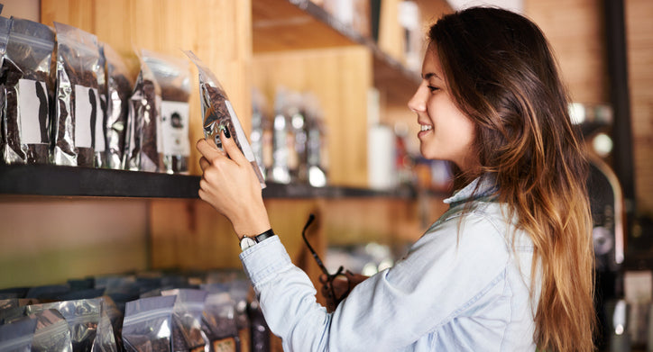 Image of a woman picking out a product from a shelf to ship to a customer from her store