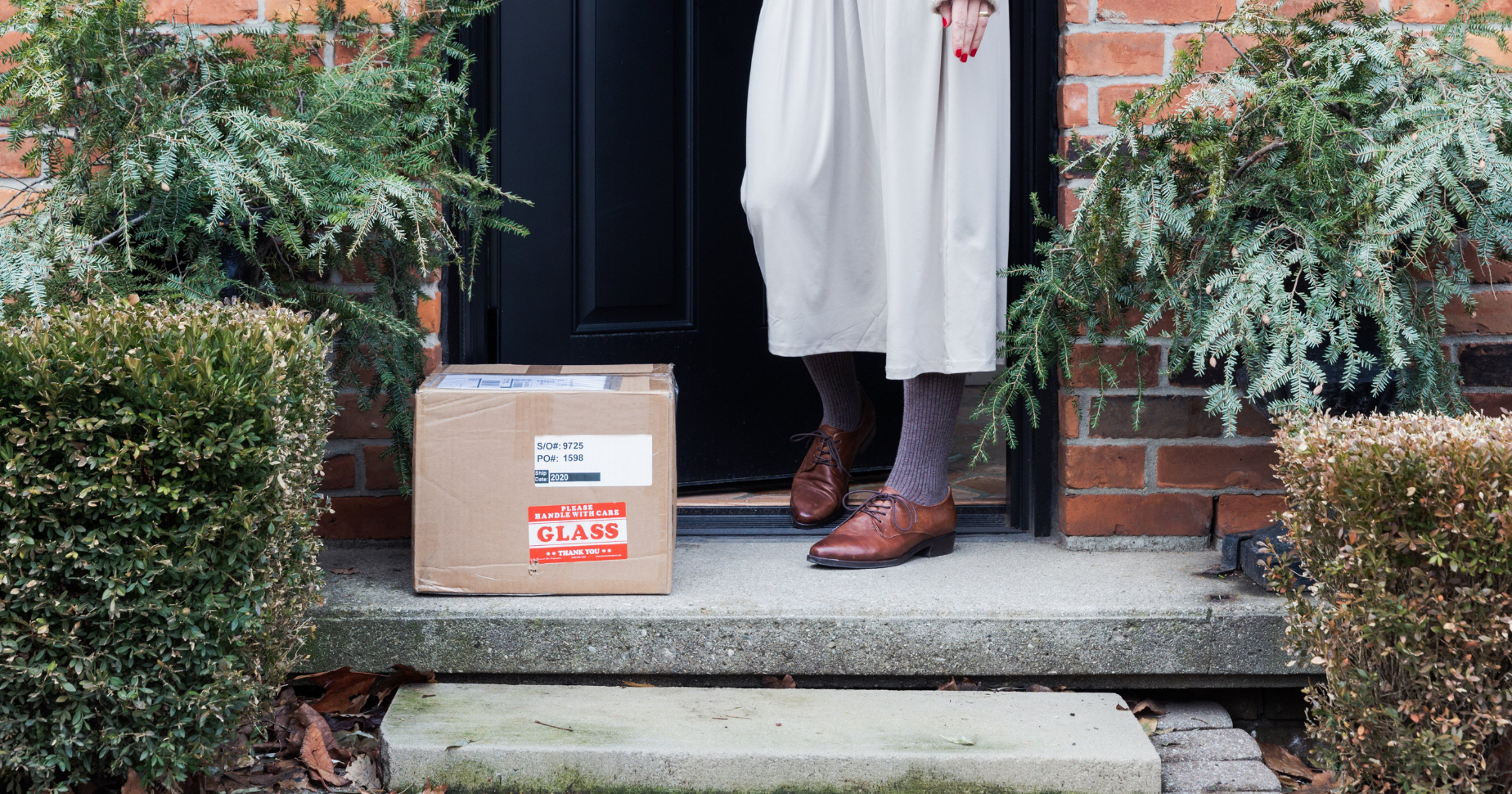 Photograph of a woman picking a package up from her doorstep