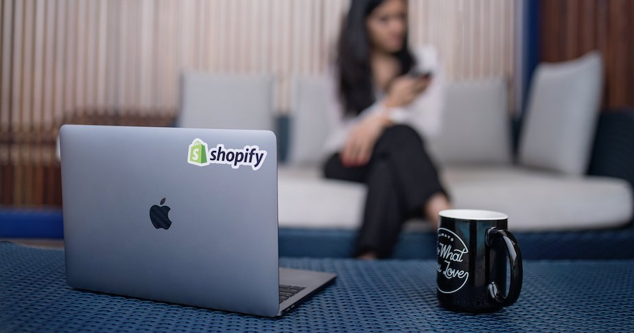 A laptop with a Shopify sticker backdropped by a women on a couch using a smartphone.
