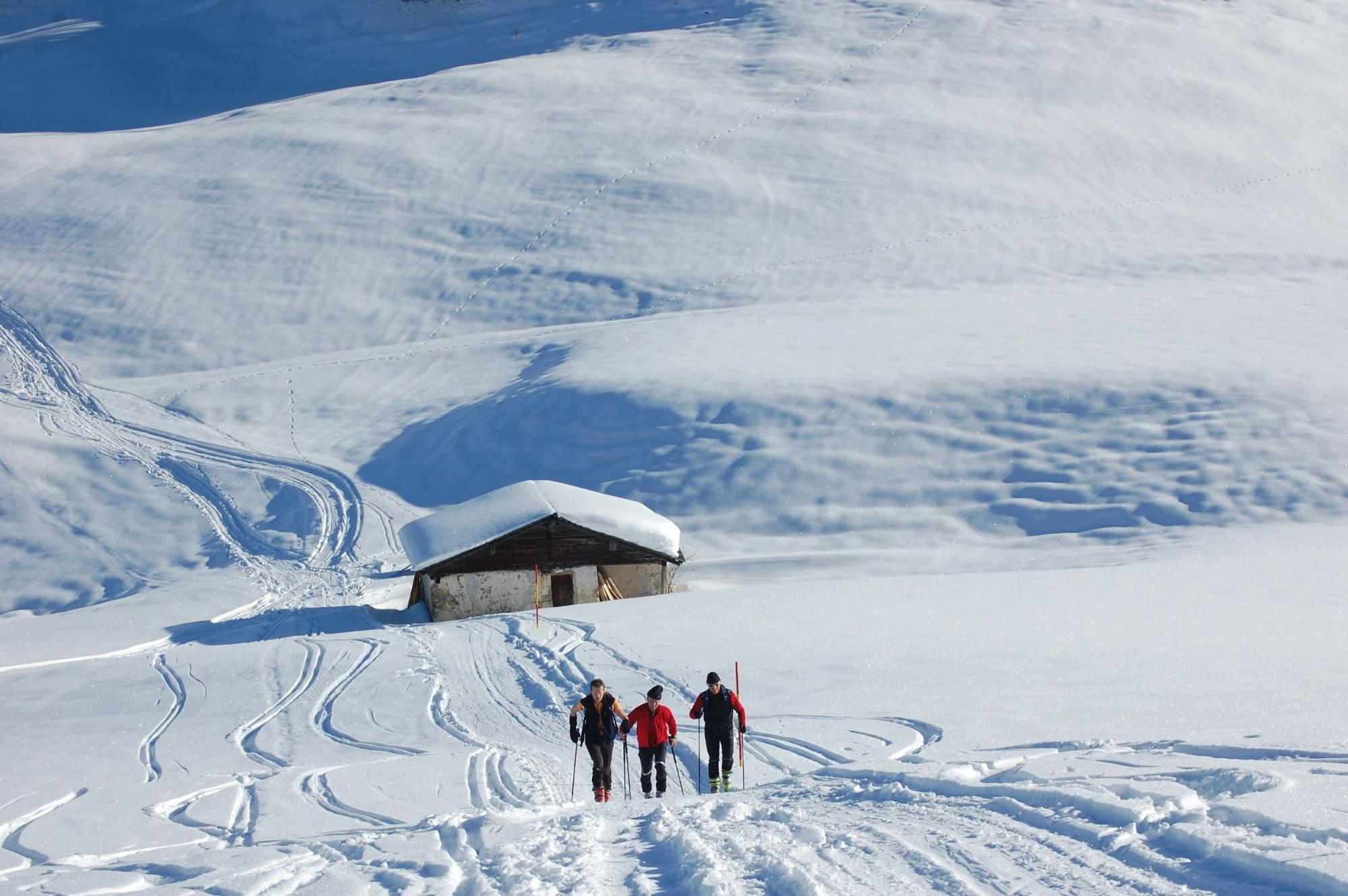 A group of three skiers walking in the snow backdropped by a chalet.