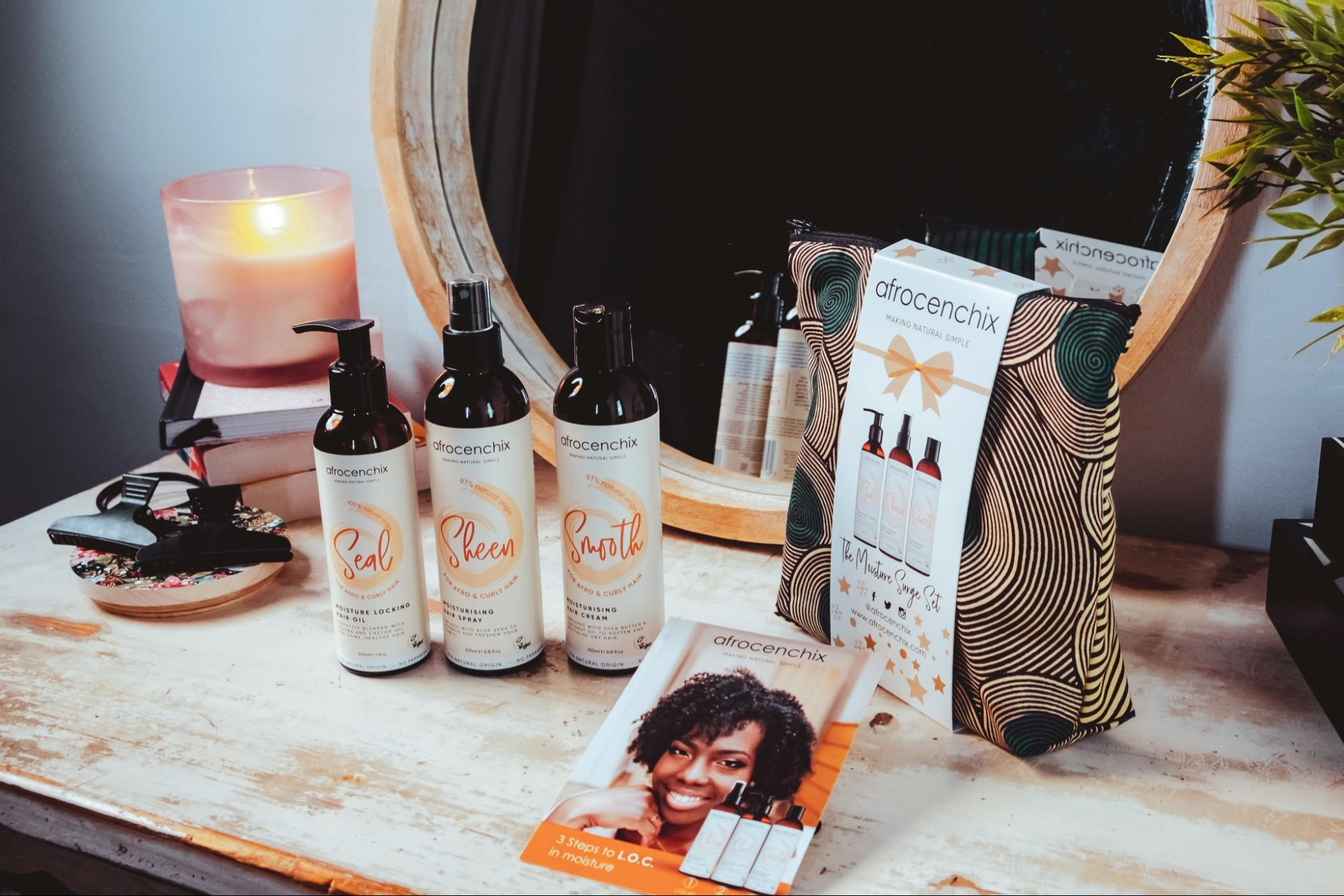 A selection of Afrocenchix products backdropped by a makeup back and mirror along with books and a candle.