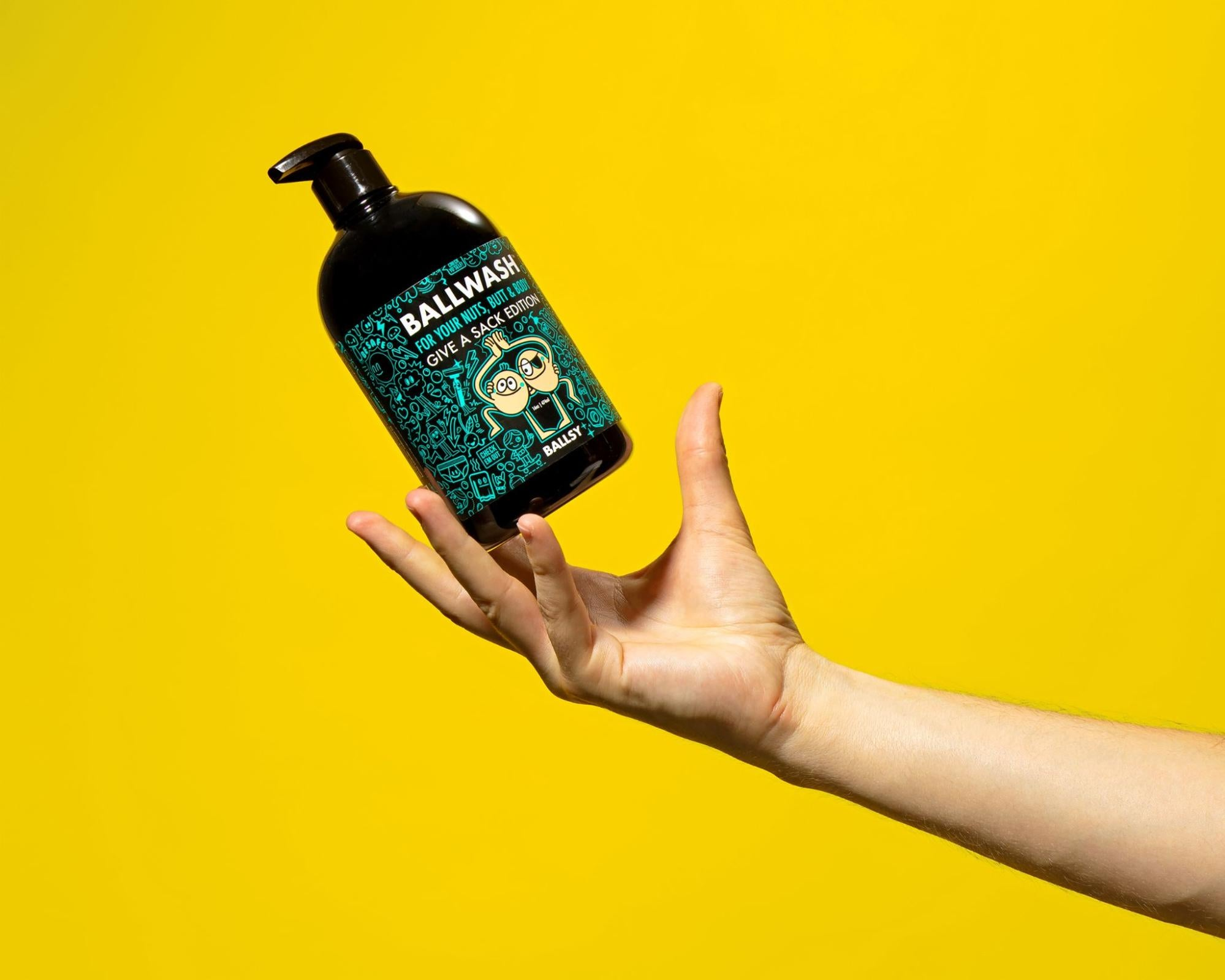 A bottle of Ballwash by Ballsy being caught my a hand model against a yellow background.
