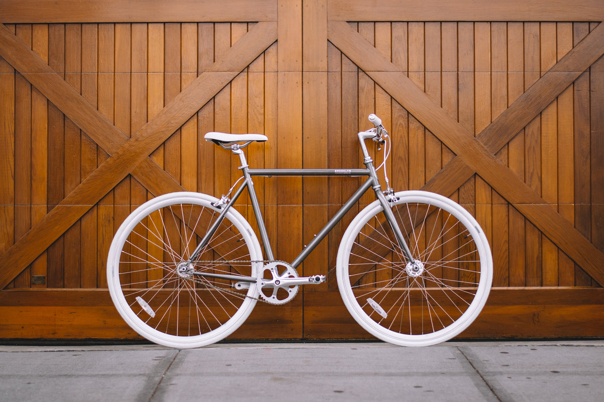 A bicycle by Brooklyn Bicycle Co. displayed against wooden doors and concrete floors.