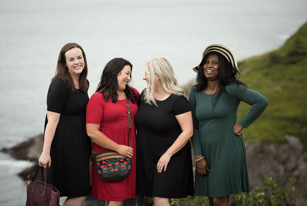 Four female models in dresses by Buttercream Clothing backdropped by cliffs and ocean settings.