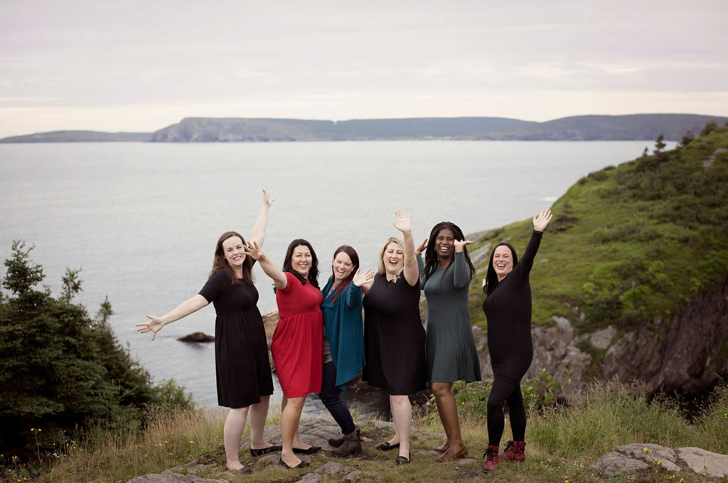 A group of five models wearing clothing from Buttercream Clothing backdropped by cliffs and ocean.