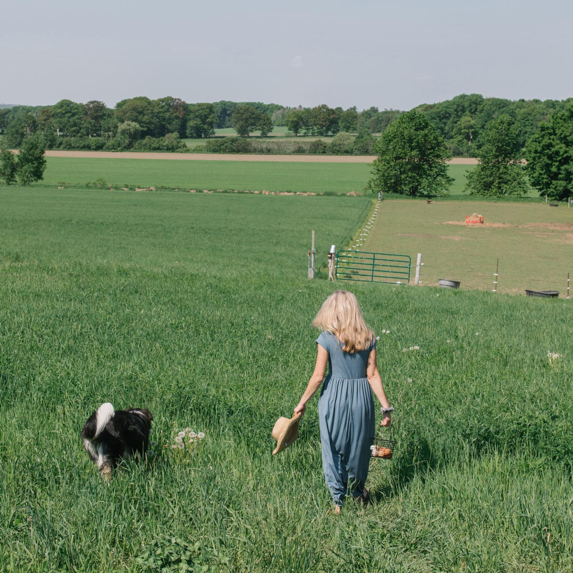 A model along with a dog in a field, wearing a blue dress from Buttercream Clothing.