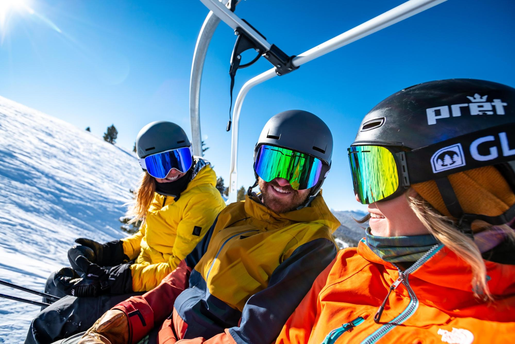 A group of three skiers on a chairlift all wearing goggles from Glade Optics.