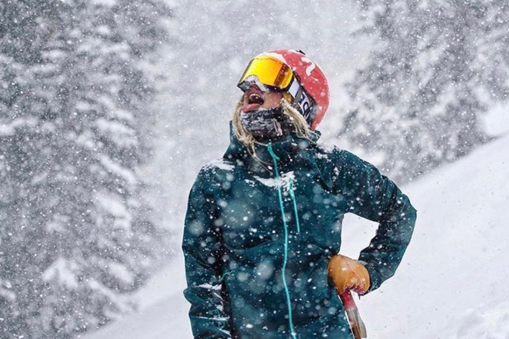 a female skier backdropped by snow hills is wearing a Glade Optics goggle.