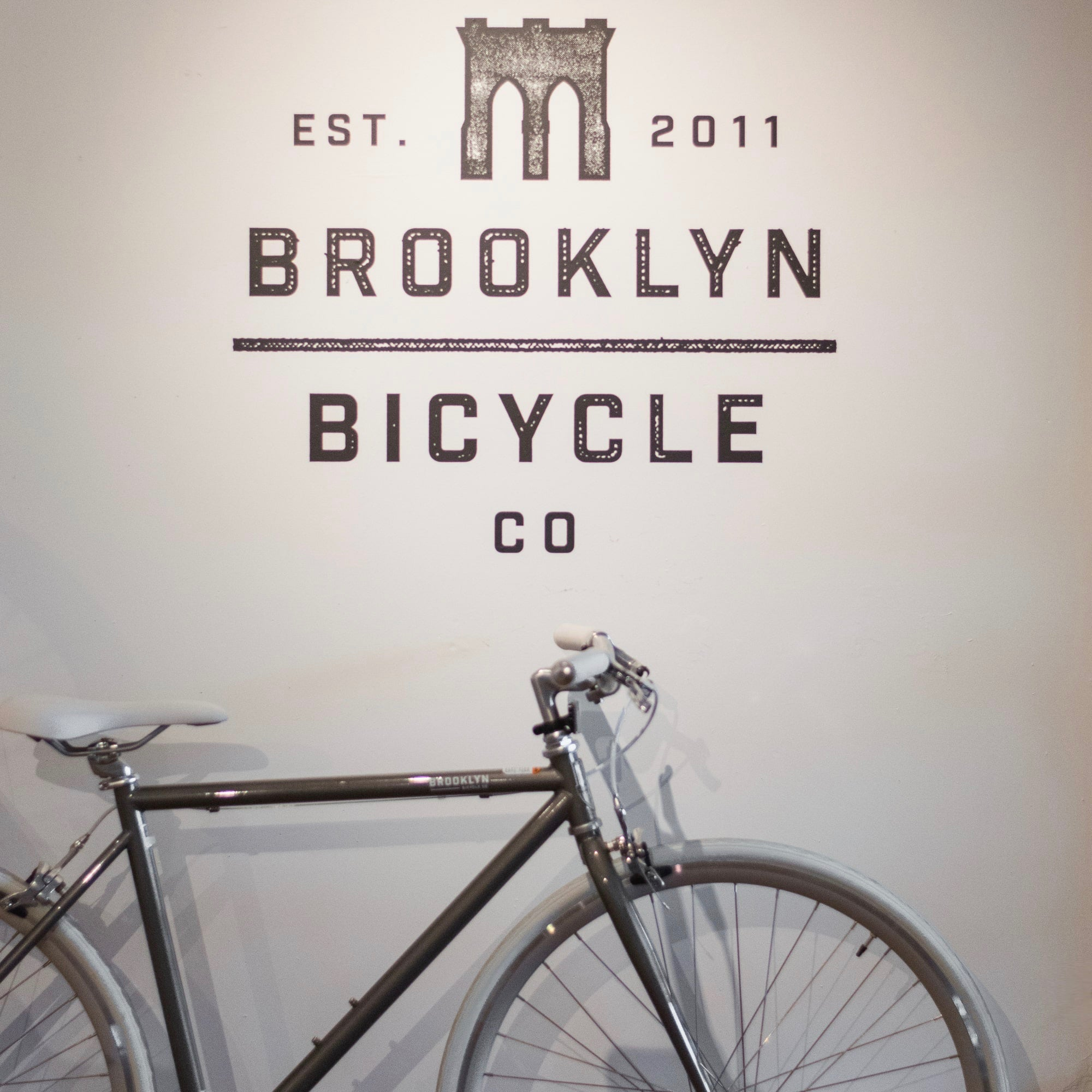 A grey bicycle by Brooklyn Bicycle Co. in their showroom against a wall with their logo.