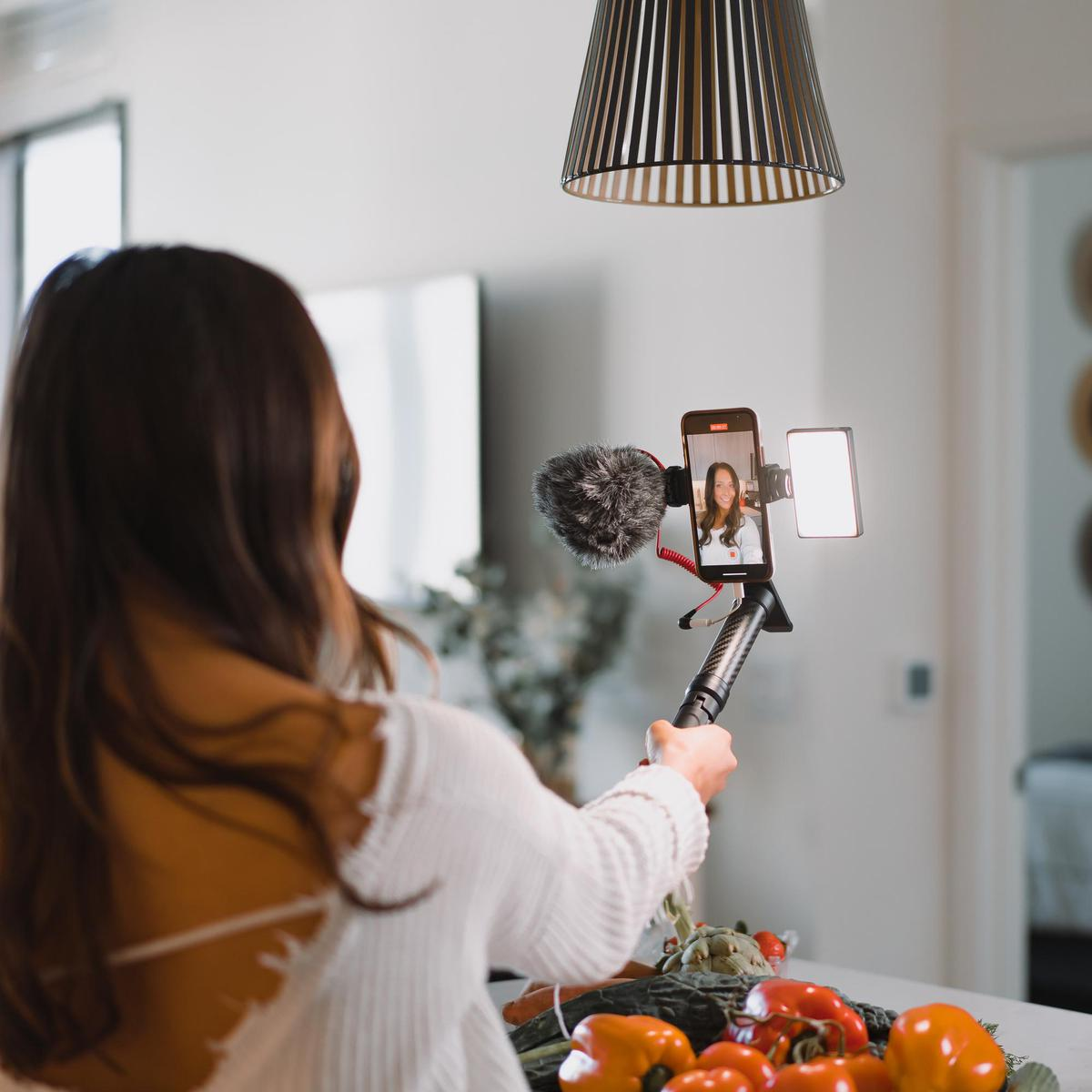 A model with a self stick, smartphone and Lume Cube lighting recording herself in a kitchen.