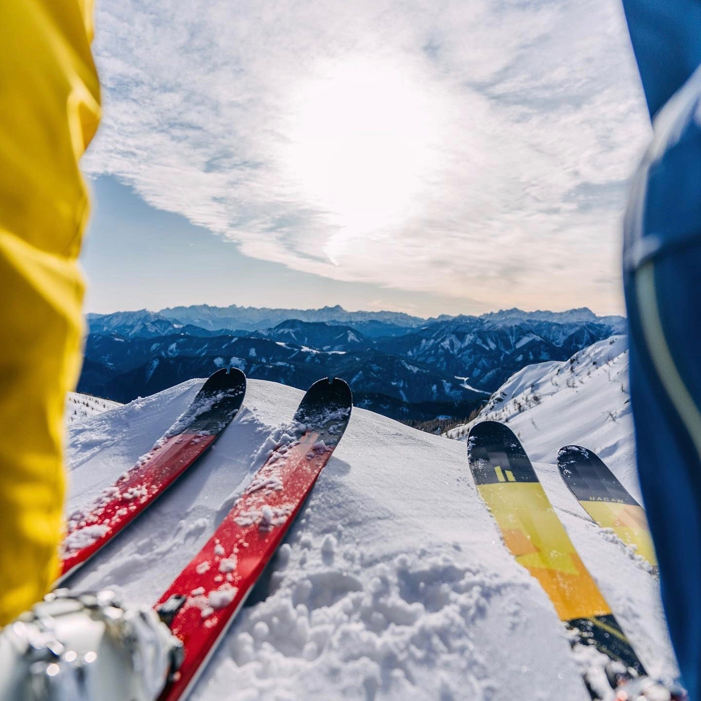 A pair of skis backdropped by snowy mountaintops.