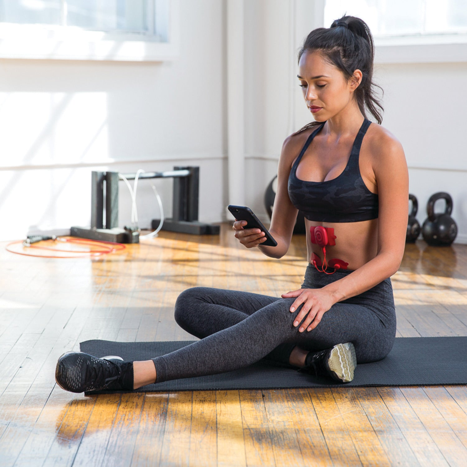 A model in workout attire using the PowerDot on her abs to stimulate pain relief.