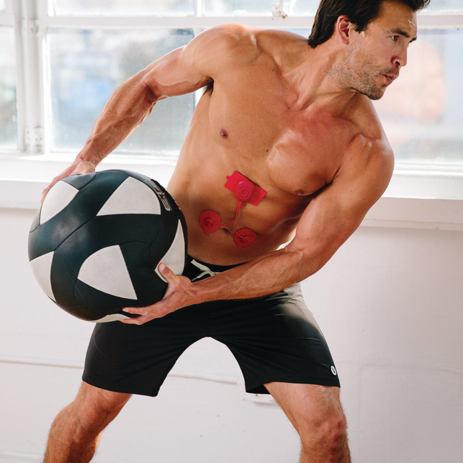 A model with an exercise hall and the PowerDot device on his abs.