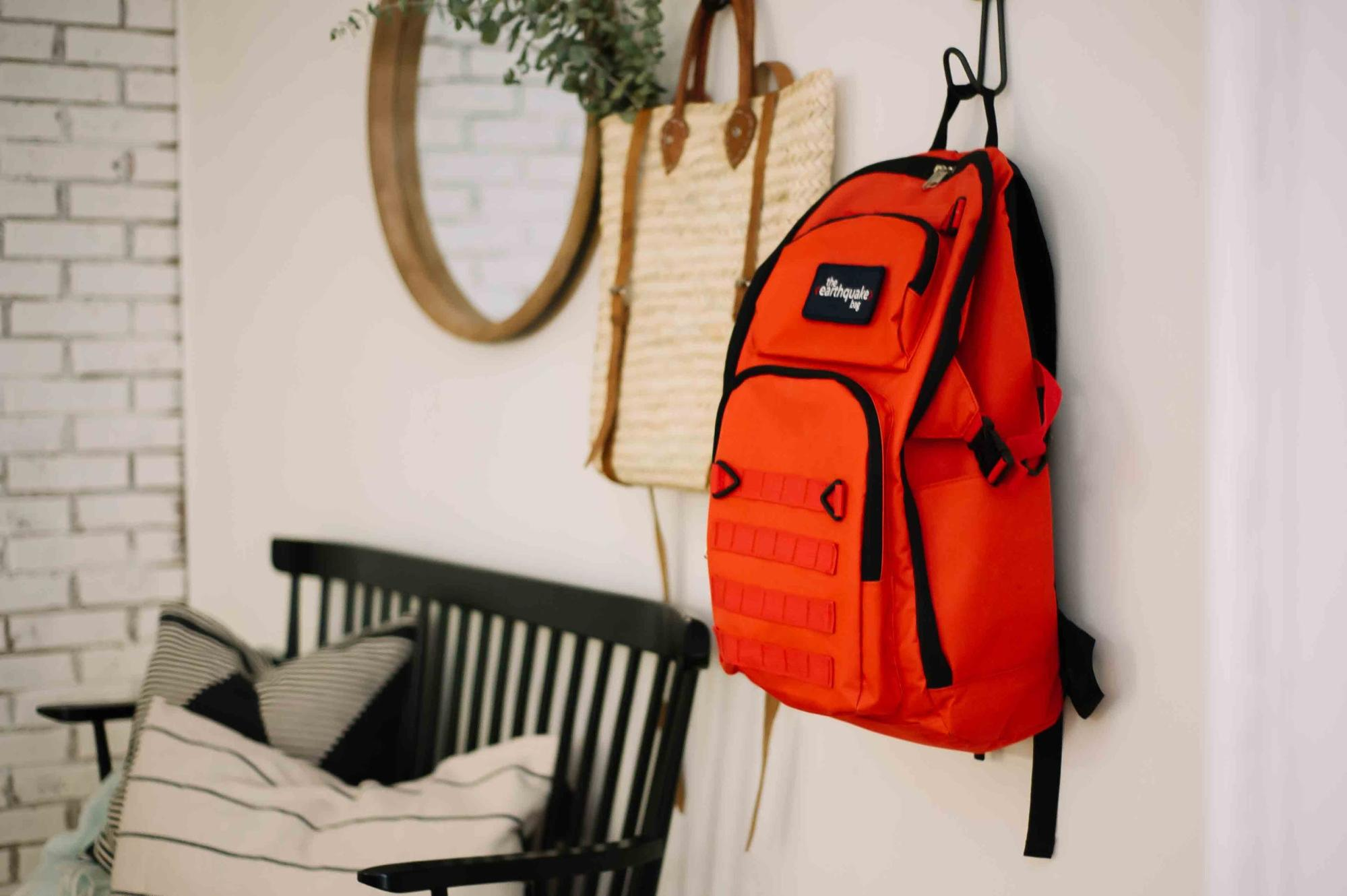 A Redfora backpack with emergency supplies on a coat hanger.