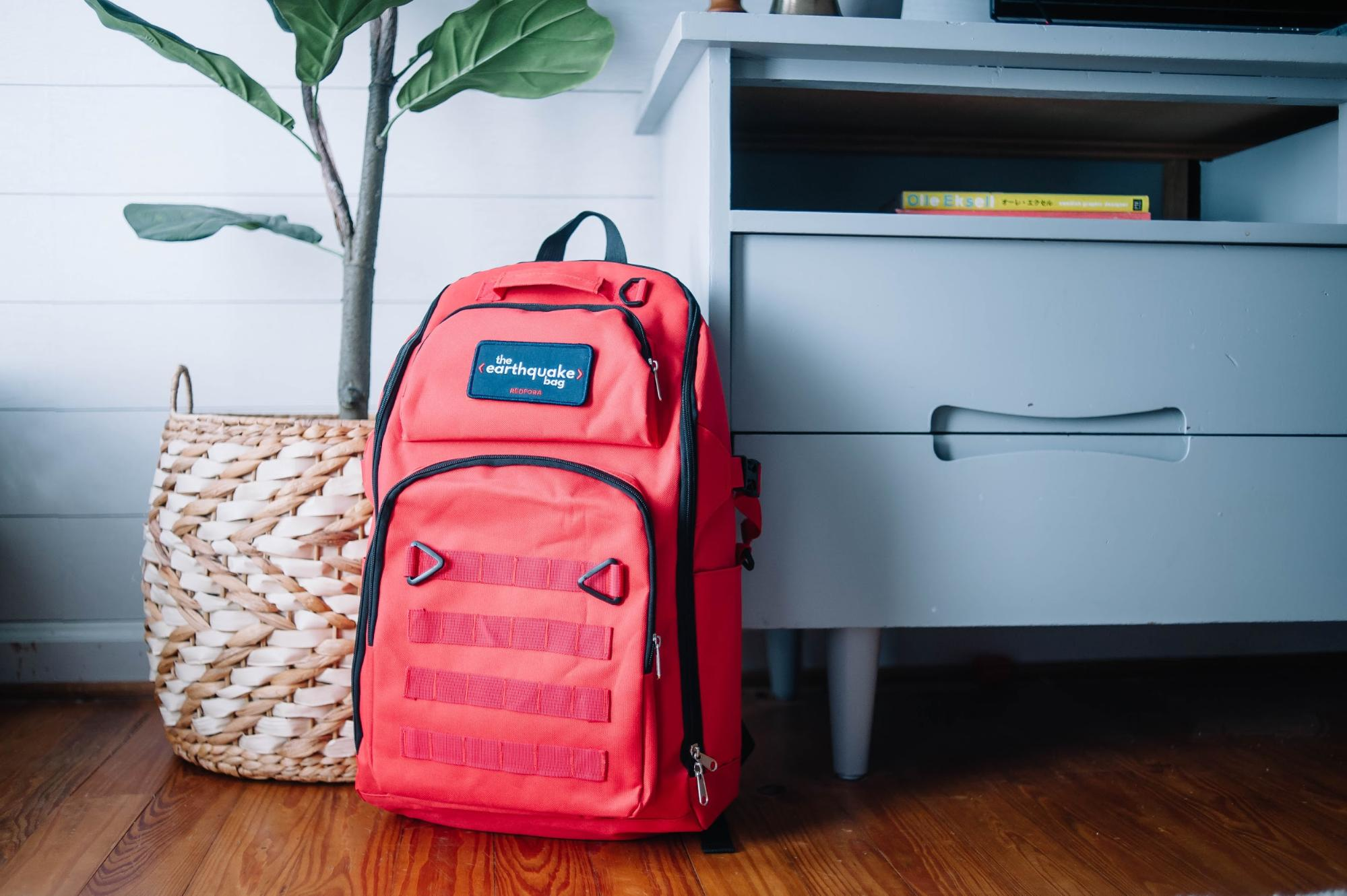 A Redfora earthquake preparedness backpack is backdropped by an end table and plant.