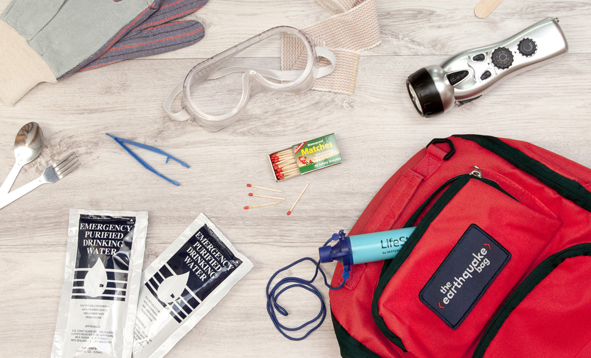A Redfora earthquake bag is laid out with its contents of purified water, matches, googles, flashlight and gloves.