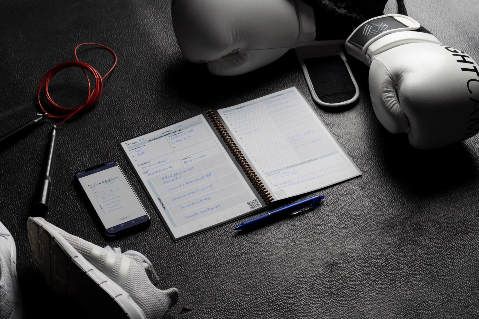 A Rocketbook notebook along with a smartphone displaying its app backdropped with workout gear like boxing gloves and running shoes.