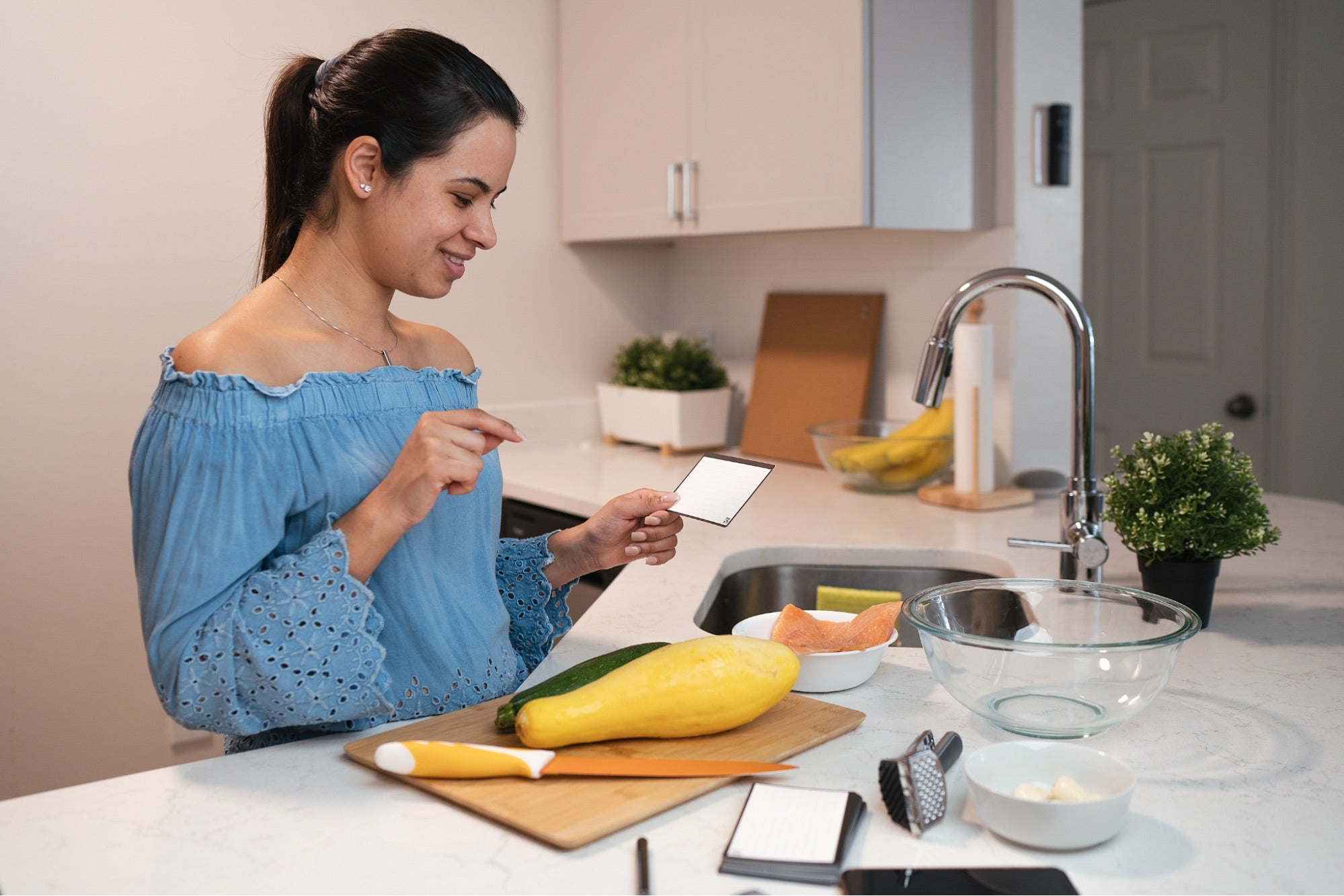 A female model using reusable note taking cards in the kitchen.