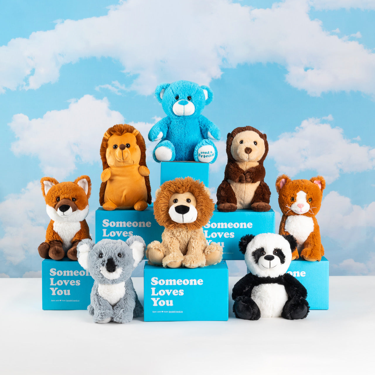An array of stuffed animals along with blue gift boxes from SendAFriend back dropped by a background with clouds painted.