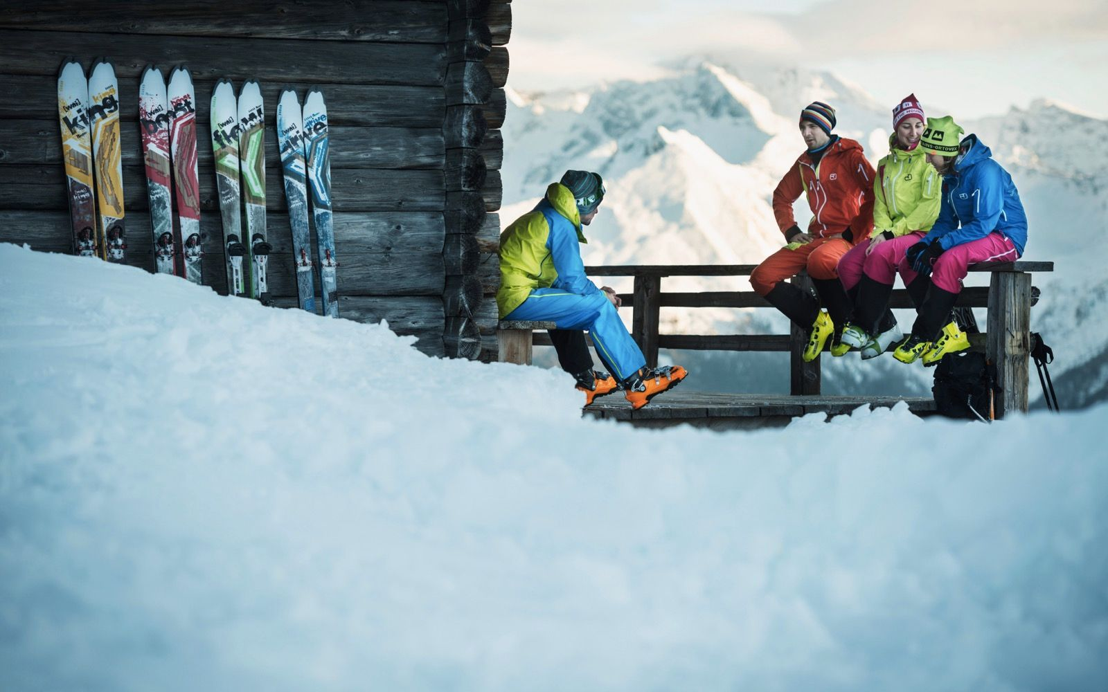 A group of four skiers sitting outside of a chalet that has pairs of skis resting on the side of the wall.