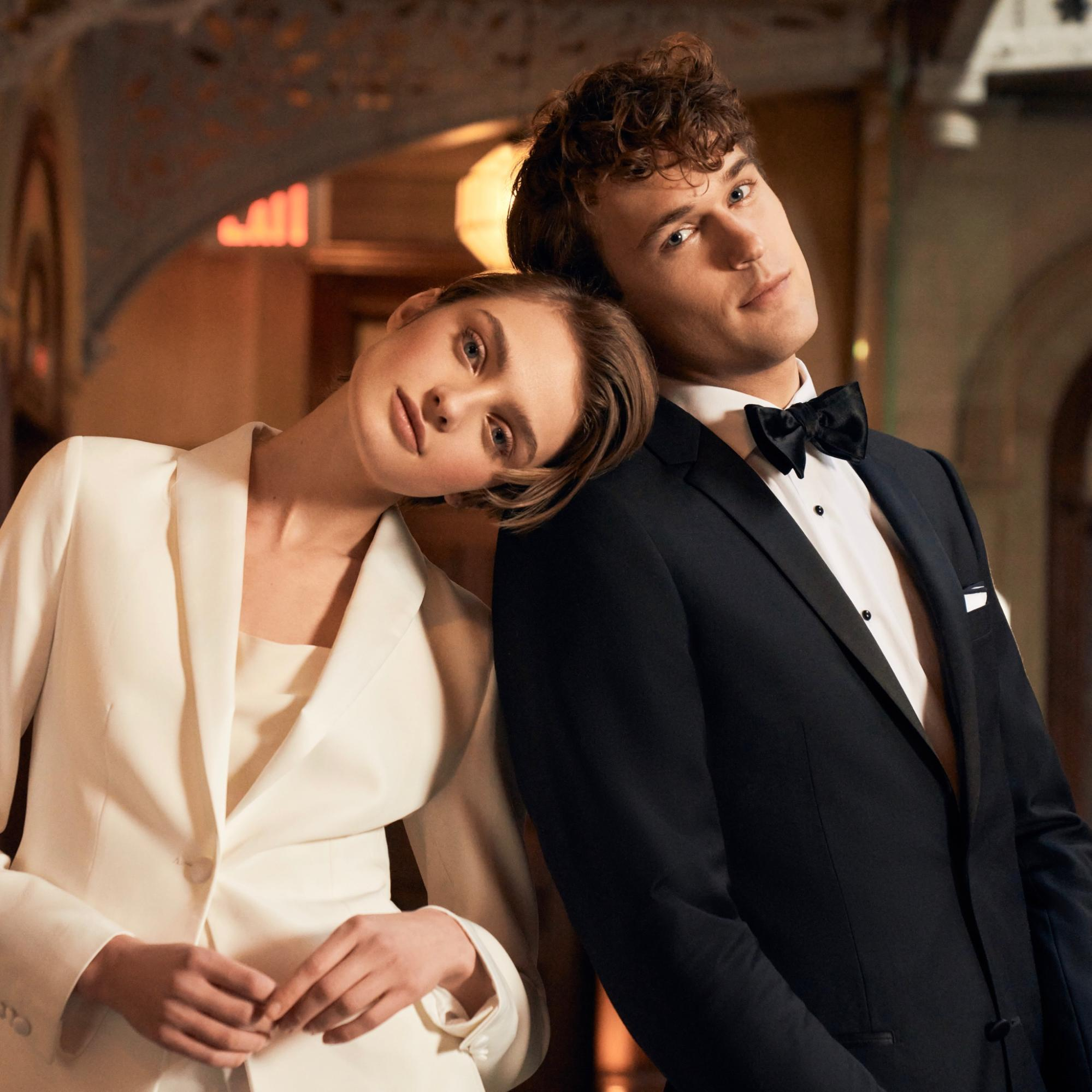 The Groomsman Suit: A female model in a white suit leans against a male model in black suit.