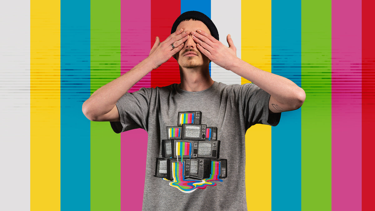 A male model wearing a Threadheads graphic t-shirt while backdropped by colorful stripes.