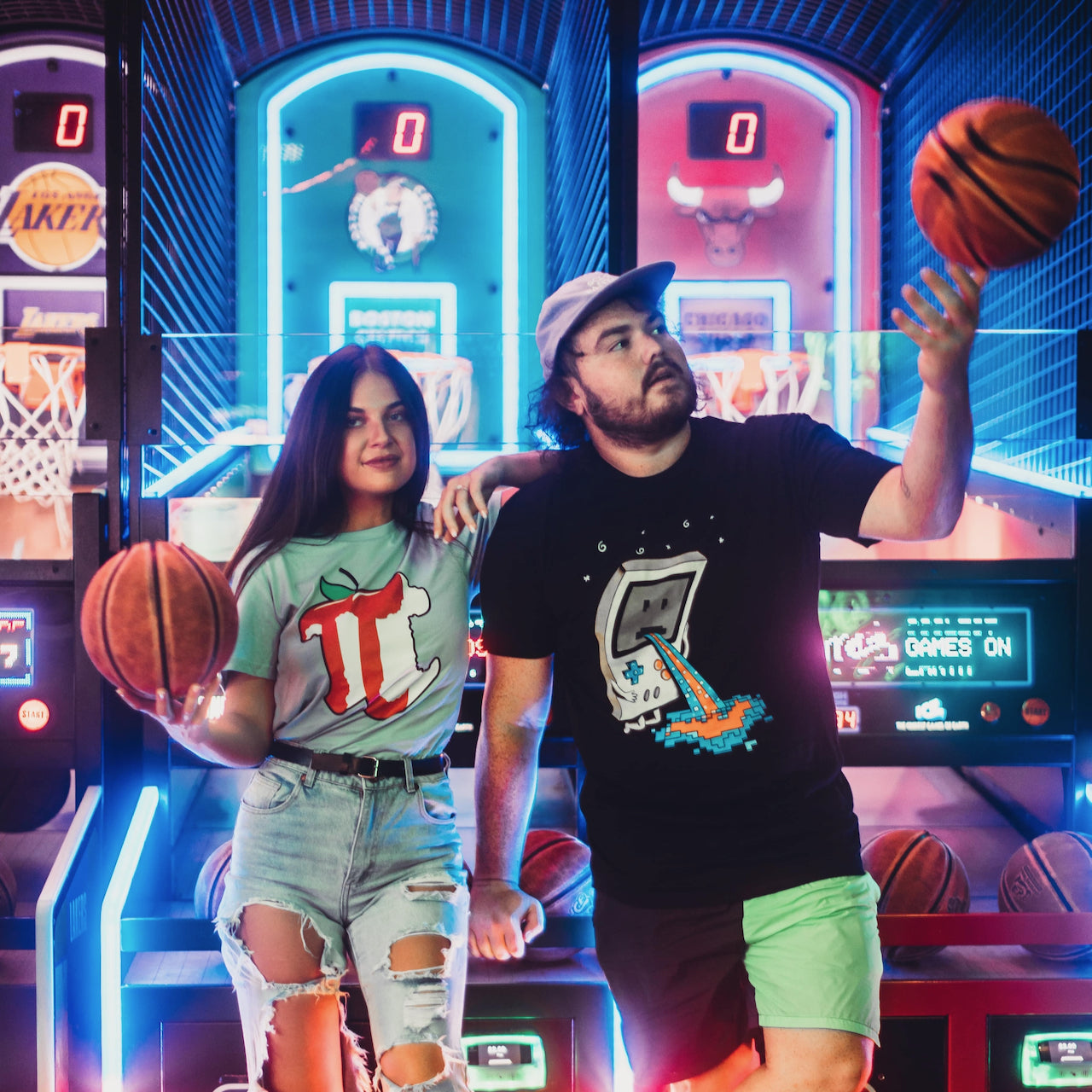 A pair of models in an arcade setting wearing T-shirts designed by Threadheads.