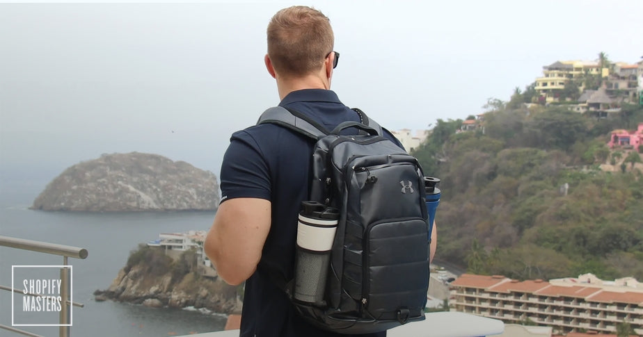 man wearing backpack with ice shaker, shopify masters logo in corner