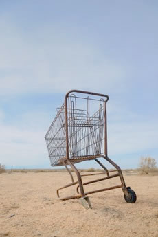 Shopping cart, bogged down in a sand dune