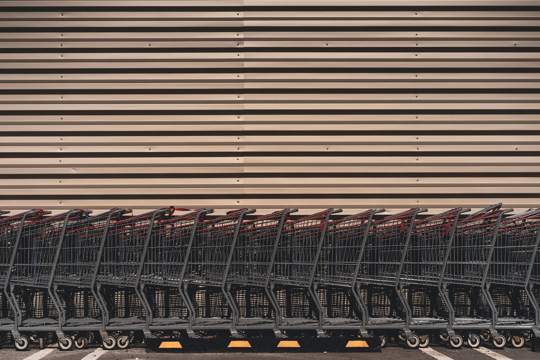 Shopping carts lined up in a straight line against a wall