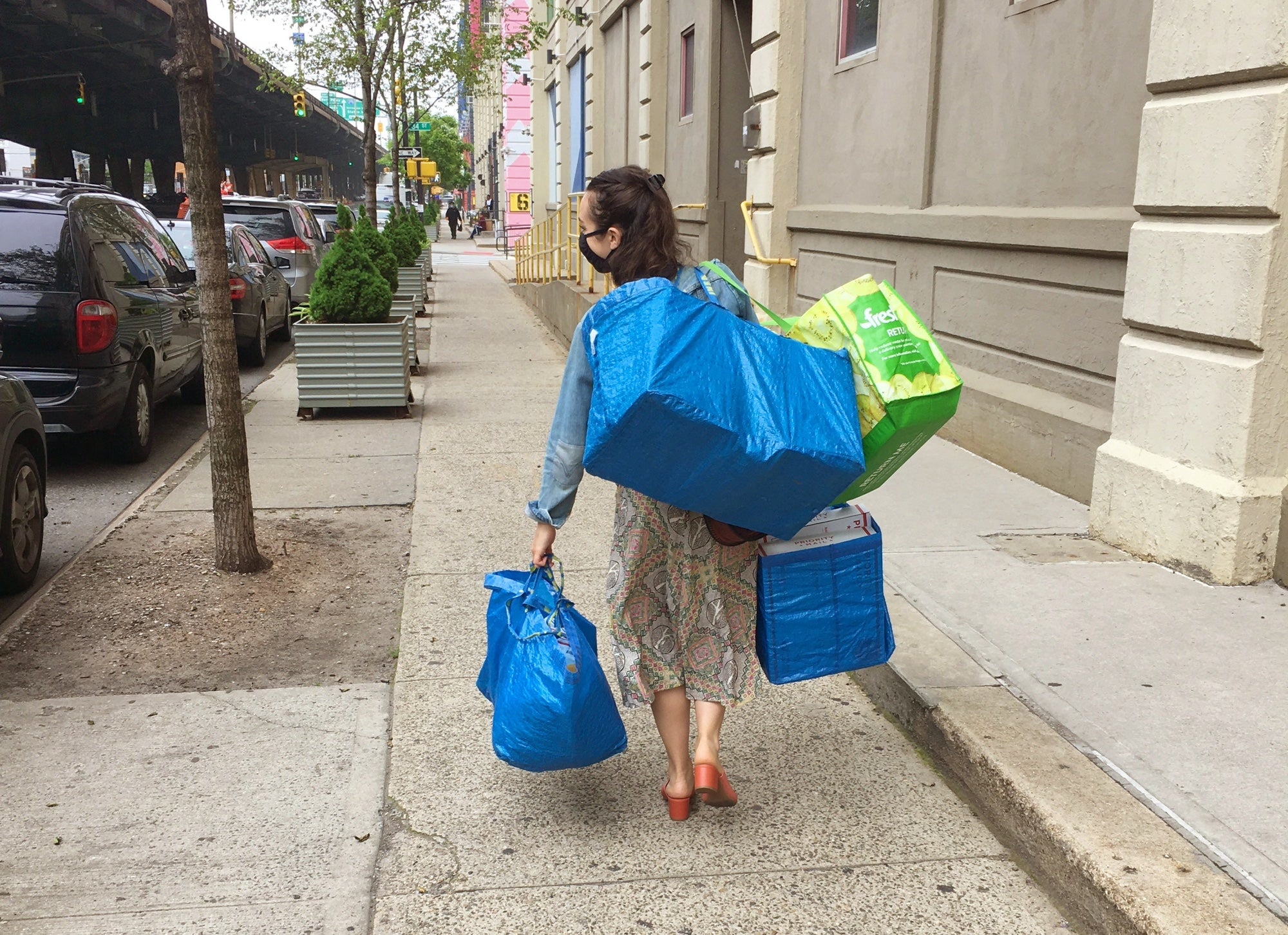 A woman carries large IKEA bags filled with vintage clothing while walking down a sidewalk