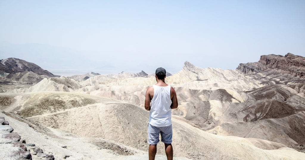 Man standing looking out over expansive sand dunes