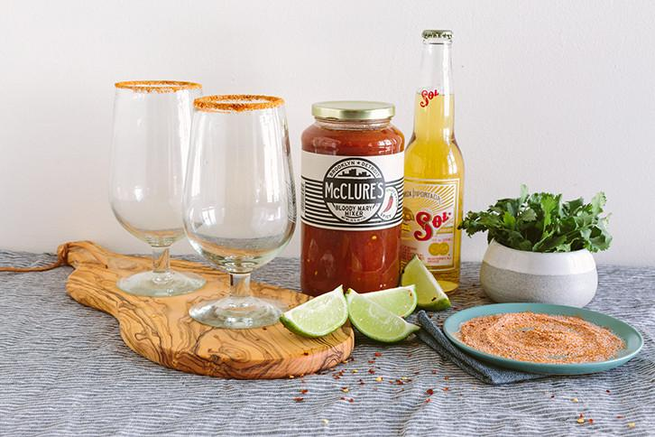 A lifestyle image of McClure's products with drinkware and ingredients