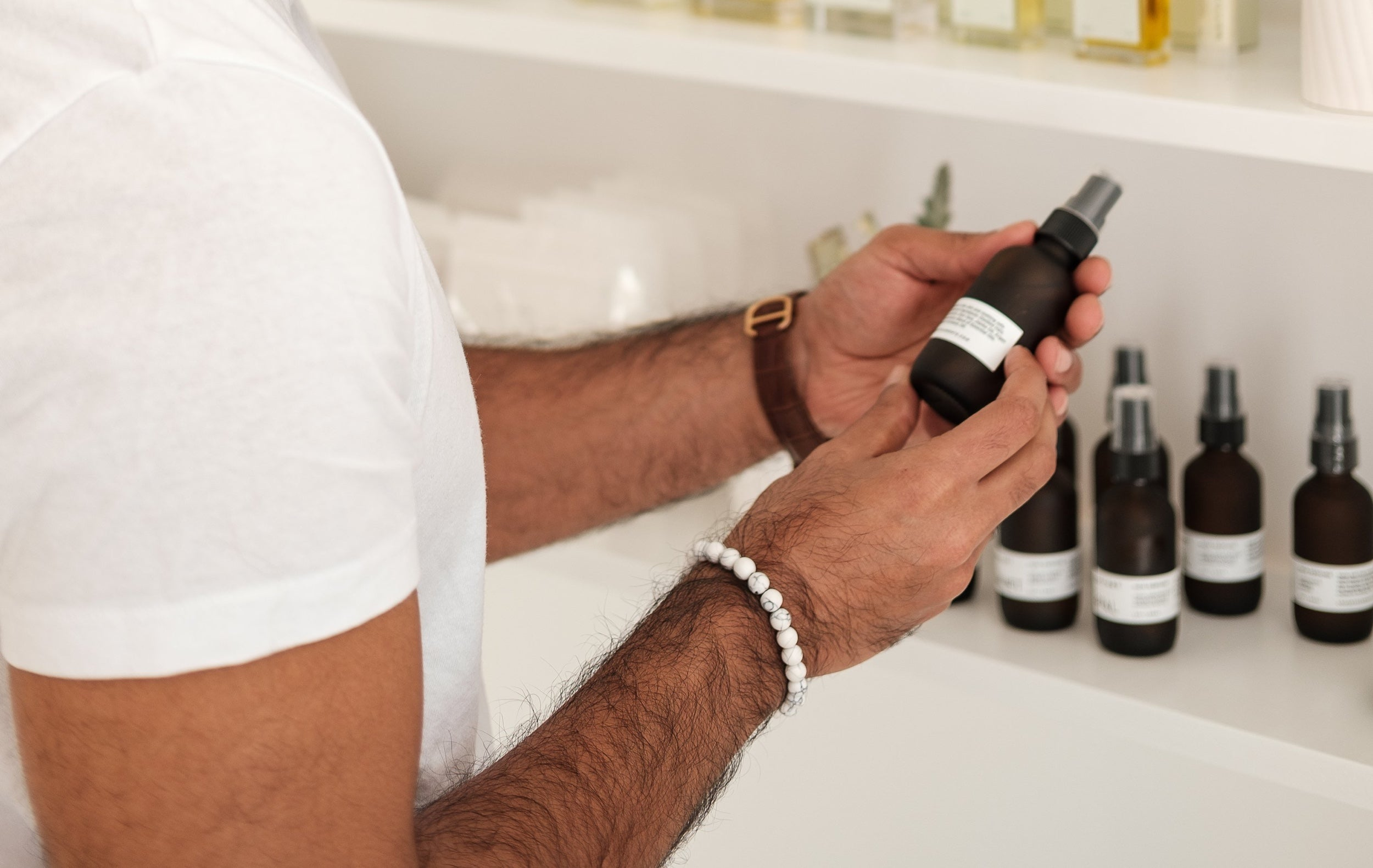 A person inspects the label of a skincare product on a shelf